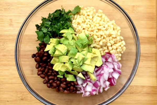 This easy recipe is a family favorite. My kids can hardly wait for it to be complete before they are digging in! Avocado Dip made with corn, beans, onions, cilantro. Delish!