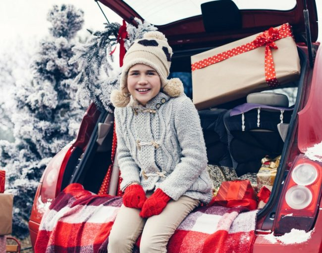 little girl on the back of a car with presents around her.