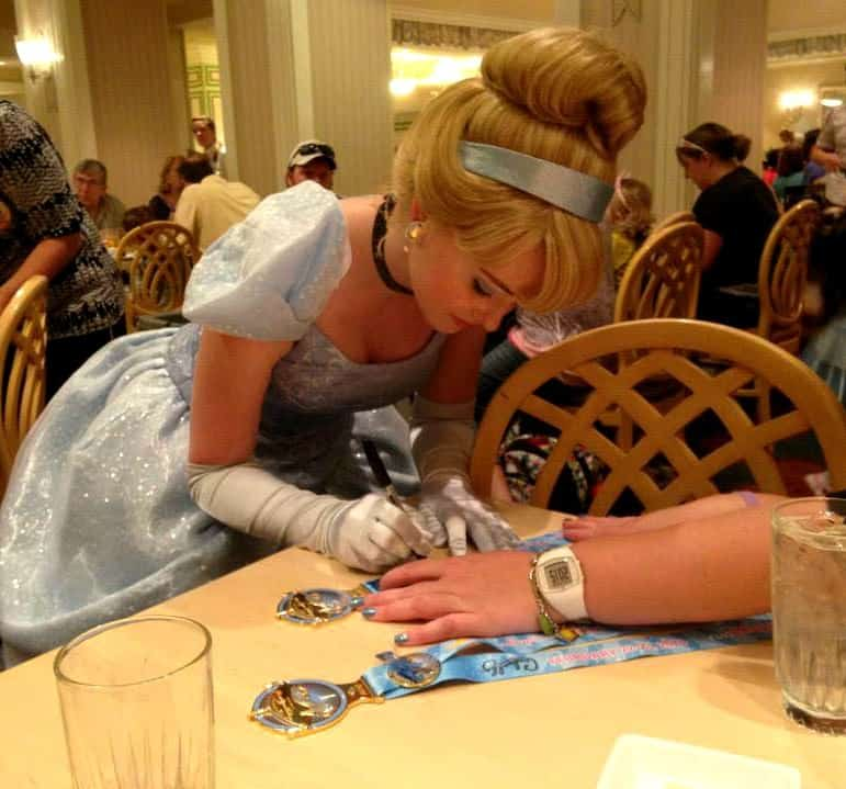 Cinderlla signing autographs on a medal ways to remember your disney vacation