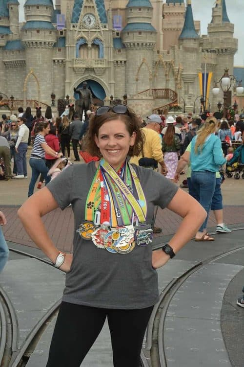 In front of castle with Dopey runDisney race medals