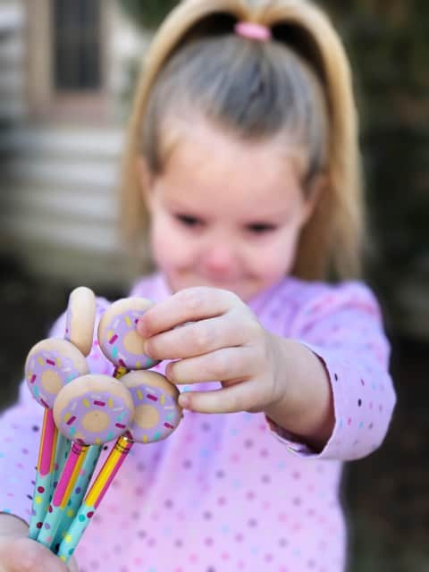 Kid holding donut erasers to go with printable Valentines cards