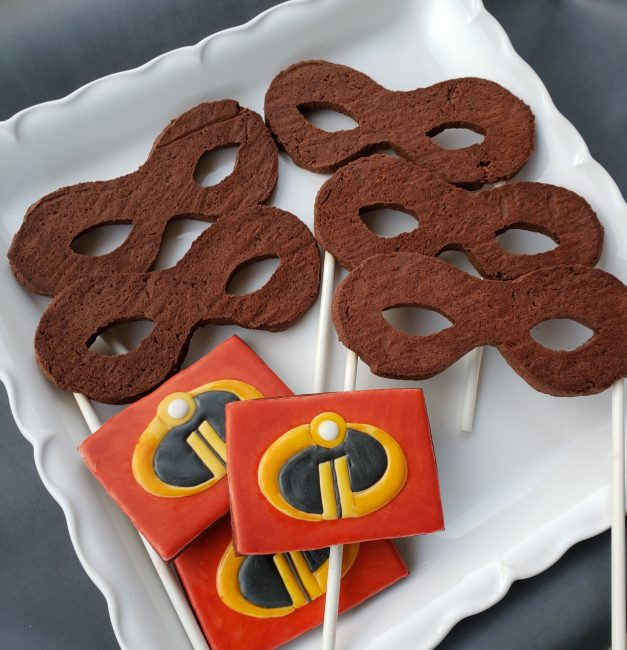 Incredibles 2 mask cookies and logo cookies for an Incredibles themed birthday party