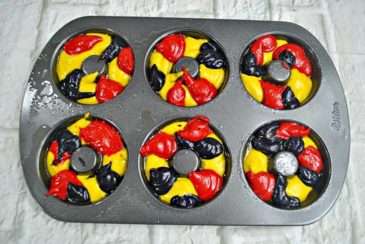 The Incredibles cake Donut in process image of red, yellow, black batter dropped in donut pan