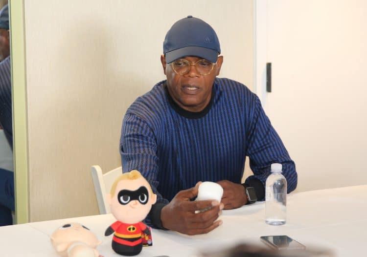 Samuel L. Jackson looking at the Incredibles toys including a Frozone Pop and Mr. Incredibles toys at Incredibles 2 Event