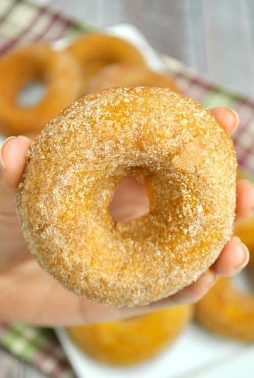pumpkin spice donuts in hand