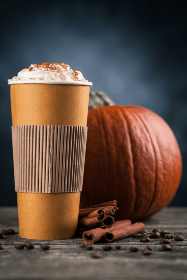 pumpkin spice latte in a paper cup with whipped cream and a pumpkin