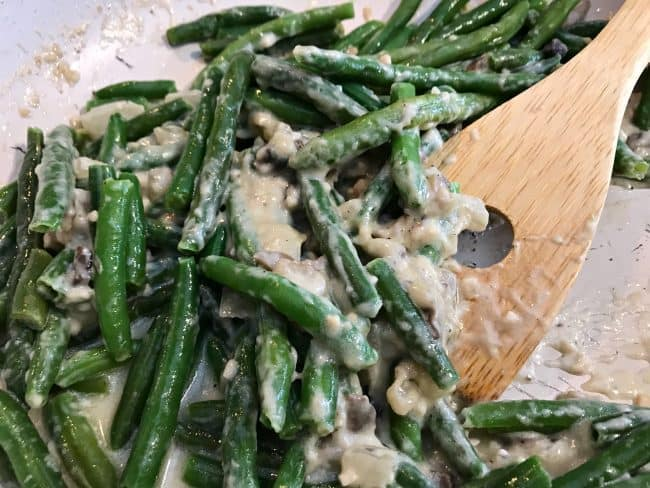 adding green beans to the keto green bean casserole