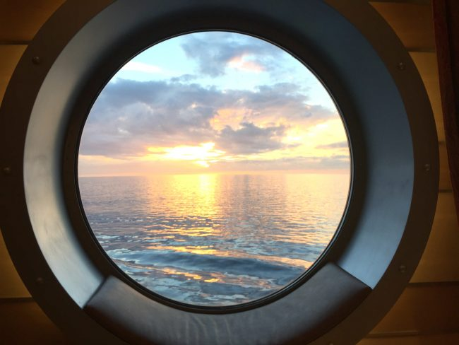 Sunset out the porthole of the Disney Dream