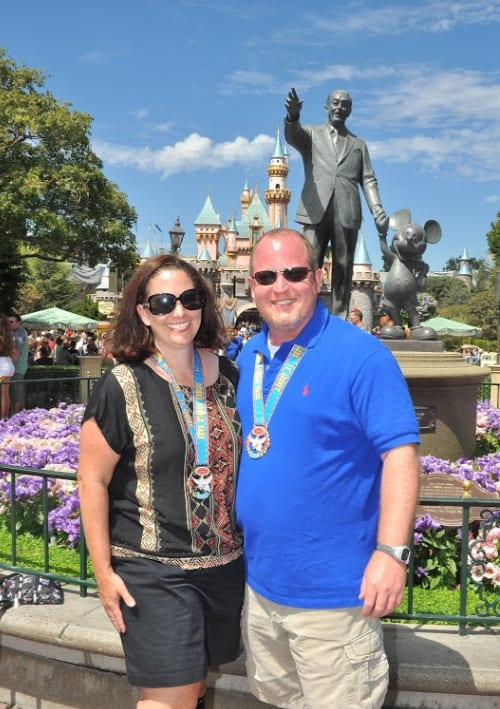 two adults in front of Sleeping Beauty castle with race medals