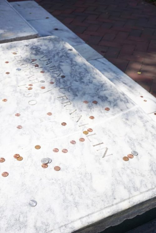 pennies on benjamin franklin grave one day in philadelphia